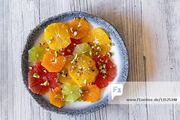 Teller mit geschälten und geschnittenen Zitrusfrüchten mit Pistazien Teller mit geschälten und geschnittenen Zitrusfrüchten mit Pistazien