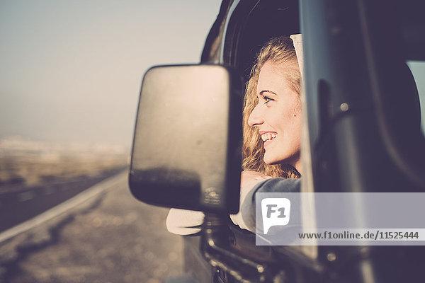 Glückliche junge Frau  die aus dem Autofenster schaut. Glückliche junge Frau, die aus dem Autofenster schaut.