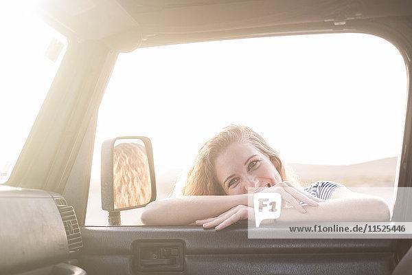 Porträt einer jungen Frau  die sich auf das Autofenster lehnt und nach innen schaut.