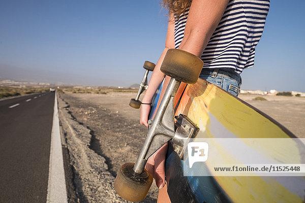 Spanien  Teneriffa  junge Frau mit Skateboard an leerer Landstraße  Teilansicht