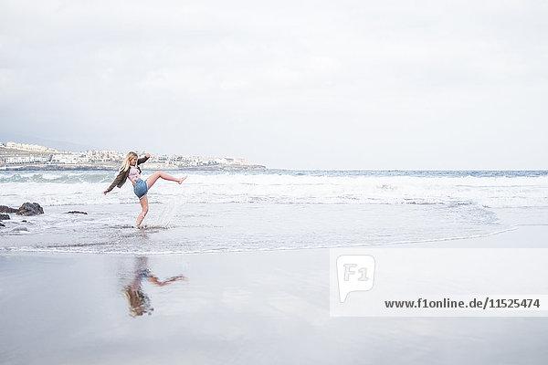 Spanien  Teneriffa  junge blonde Frau am Strand