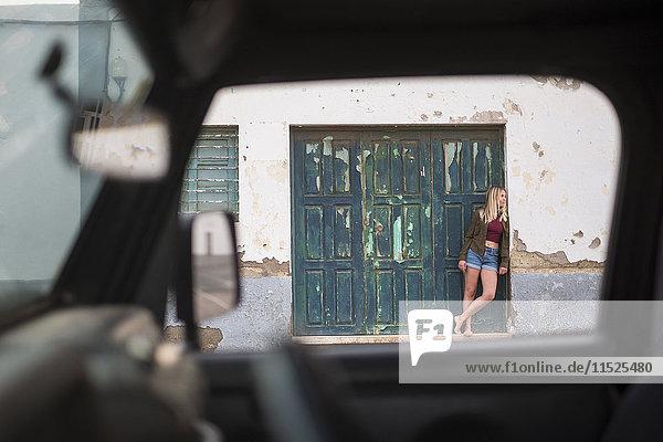 Spanien  Teneriffa  junge blonde Frau an der Wand vor einer Holztür lehnend