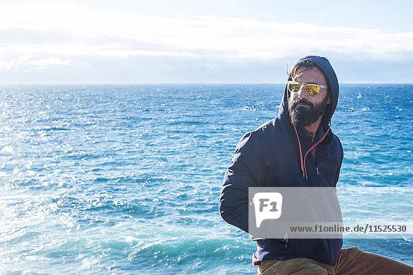 Porträt eines Mannes mit verspiegelter Sonnenbrille und Kapuzenjacke vor dem Meer