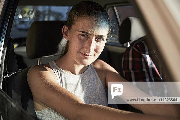 Porträt eines jungen Autofahrers  der aus dem Autofenster blickt