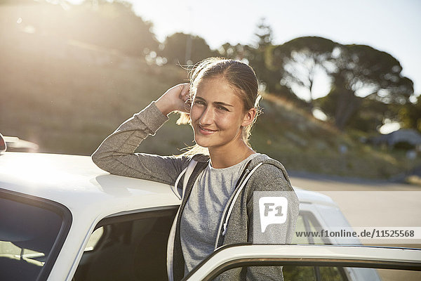 Portrait of smiling young woman leaning on car roof