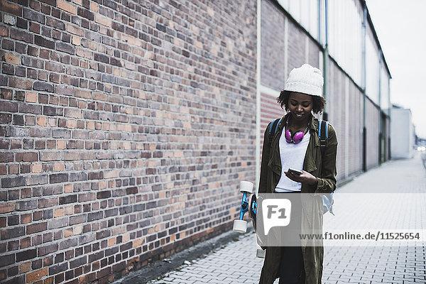 Junge Frau mit Kopfhörer  Rucksack und Skateboard beim Blick aufs Handy