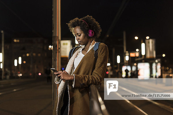 Young woman with headphones and smartphone waiting at the tram stop