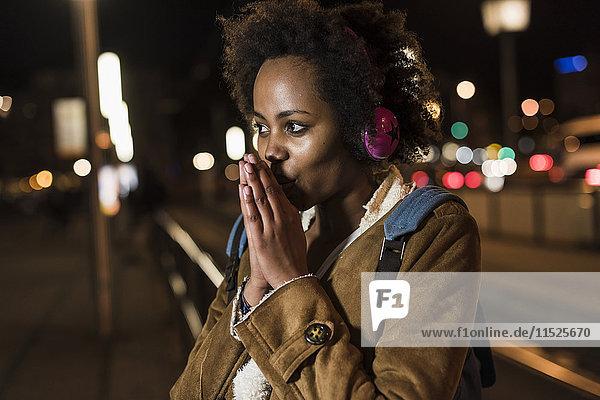 Junge Frau hört Musik mit Kopfhörern  während sie an der Straßenbahnhaltestelle wartet.