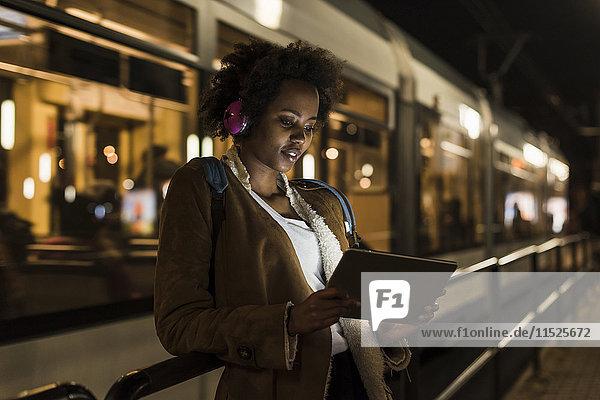 Junge Frau mit Kopfhörer und Tablette wartet an der Straßenbahnhaltestelle