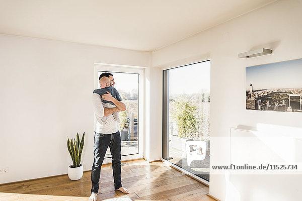 Vater hält und umarmt seinen kleinen Sohn  steht im gemütlichen Heim