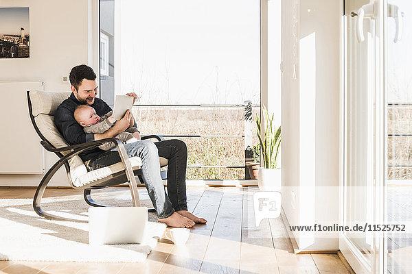 Vater im Sessel sitzend mit Sohn auf dem Schoß  mit mobilen Geräten