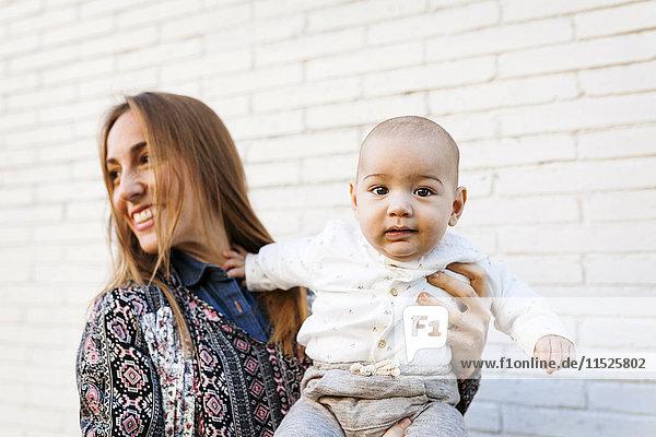 Glückliche Mutter mit Baby an der Ziegelwand