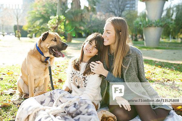 Mutter und Tochter mit Hund im Park