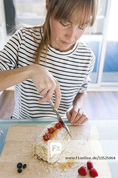 Junge Frau zerschneidet veganen Kuchen
