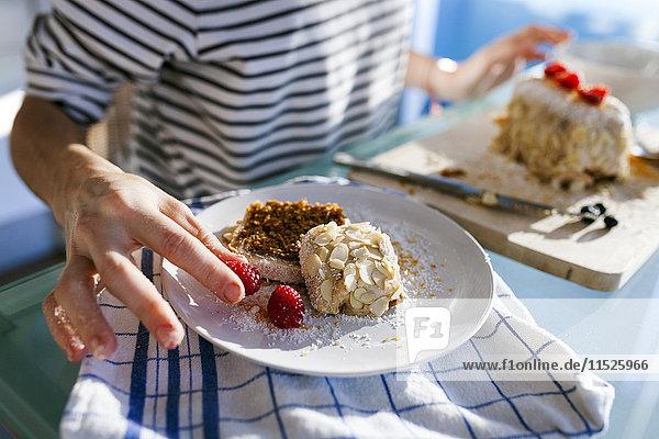Junge Frau beim Garnieren von veganem Kuchen