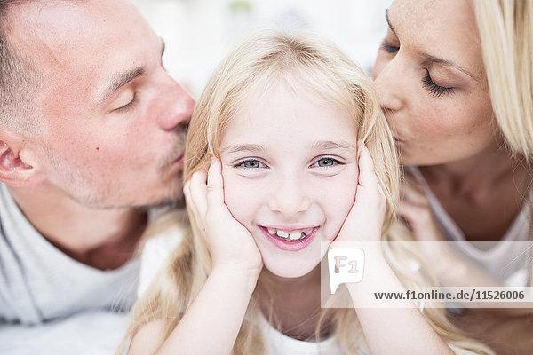 Porträt eines lächelnden Mädchens  das von den Eltern geküsst wird.