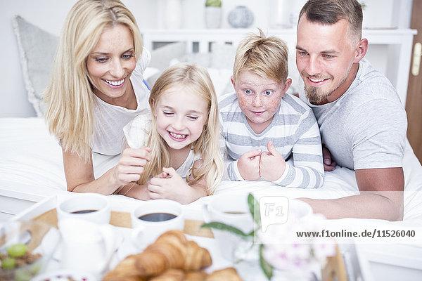 Glückliche Familie beim Frühstück im Bett