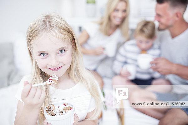 Porträt eines lächelnden Mädchens beim Essen aus der Müslischale mit Familie im Hintergrund