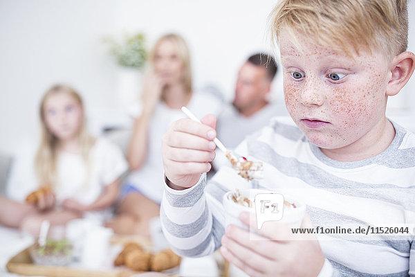 Junge starrt auf Müslischale mit Familie im Hintergrund