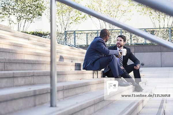 Zwei Geschäftsleute sitzen auf einer Treppe und reden.