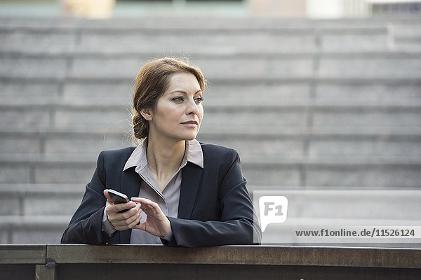 Businesswoman holding cell phone outdoors looking away