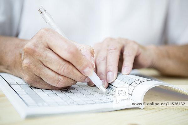 Nahaufnahme einer älteren Frau bei einem Kreuzworträtsel