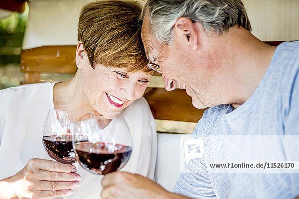 Glückliches Seniorenpaar bei einem Glas Rotwein