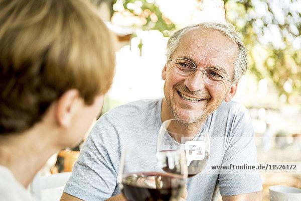 Lächelndes älteres Paar klirrende Rotweingläser im Freien