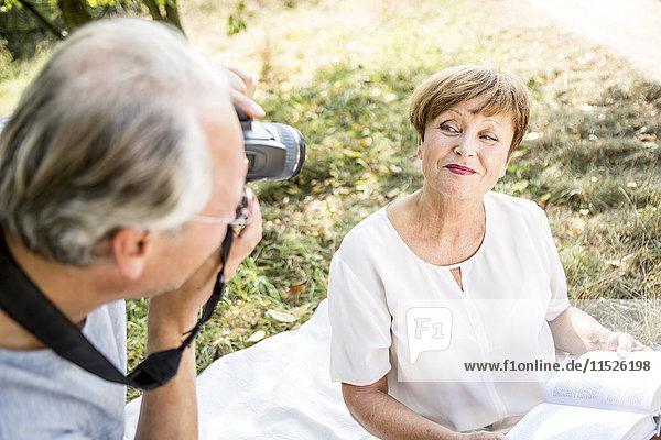 Älterer Mann beim Fotografieren seiner Frau auf der Wiese