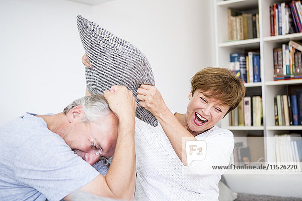 Sorgenfreies Seniorenpaar zu Hause bei einer Kissenschlacht