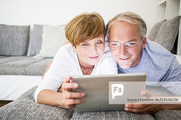 Seniorenpaar zu Hause auf der Couch liegend mit digitalem Tablett