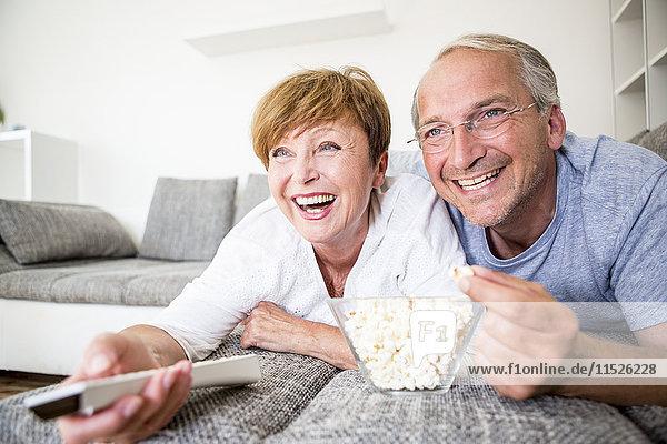 Glückliches älteres Paar zu Hause  das auf der Couch liegt und fernsieht.