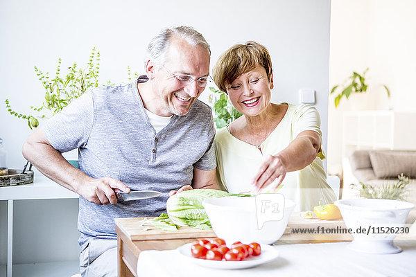 Fröhliches Seniorenpaar in der Küche beim gemeinsamen Salat zubereiten