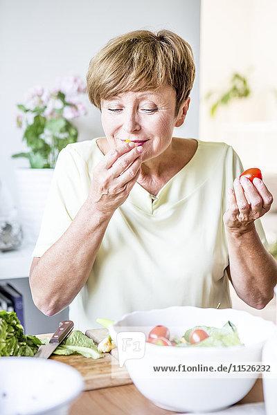 Seniorin in der Küche bei der Zubereitung von Salat