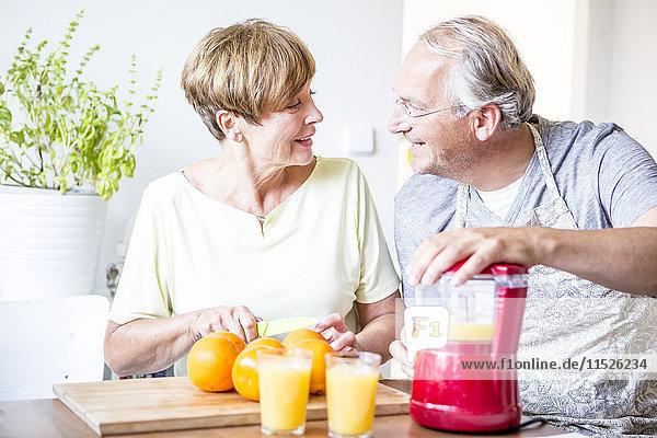 Seniorenpaar in der Küche bereitet frisch gepressten Orangensaft zu.