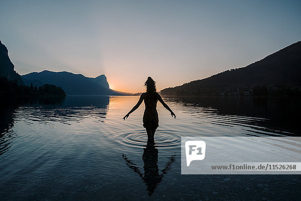 Österreich  Mondsee  Mondsee  Silhouette der im Wasser stehenden Frau bei Sonnenuntergang