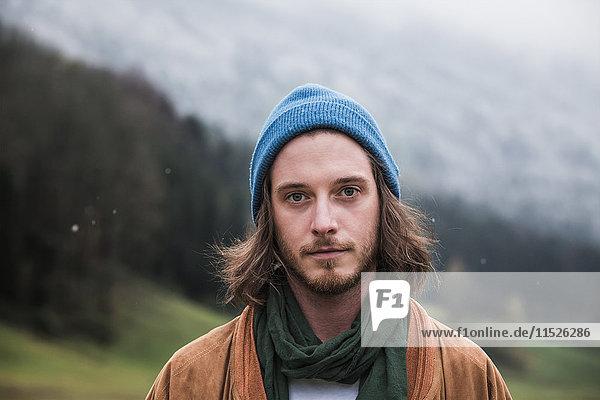 Porträt eines bärtigen jungen Mannes im Herbst mit blauer Mütze Porträt eines bärtigen jungen Mannes im Herbst mit blauer Mütze