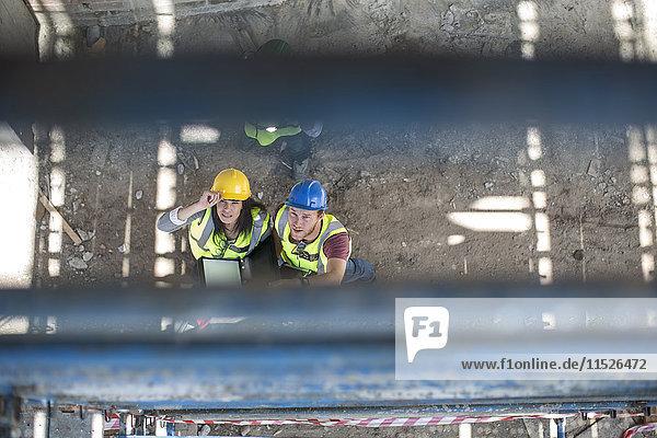 Bauarbeiter im Gespräch mit einer Frau auf einer Baustelle