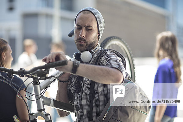 Junger Mann  der das Fahrrad hält und die Zeit überprüft.