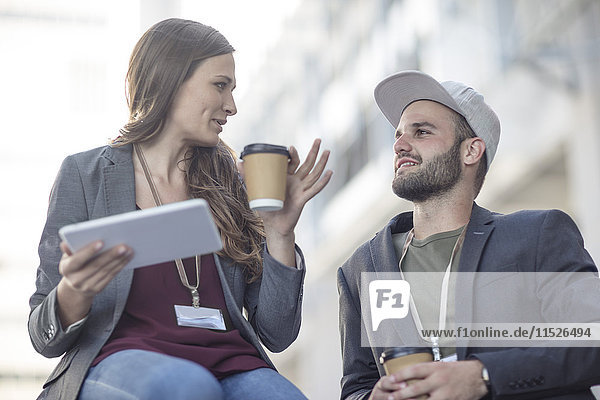 Young man and woman with tablet and coffee to go talking outdoors