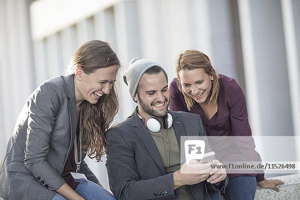 Drei fröhliche junge Leute schauen gemeinsam aufs Handy