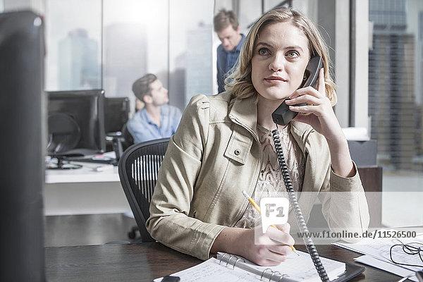 Junge Frau am Schreibtisch im Büro am Telefon