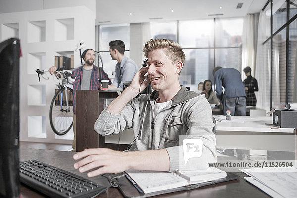 Junger Mann am Schreibtisch im Büro mit Headset