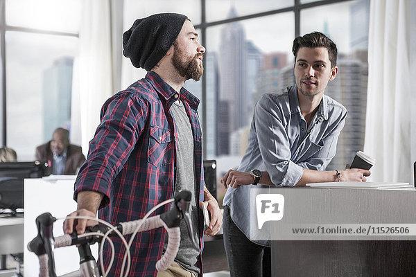 Lässiger Mann mit Fahrrad im modernen Büro