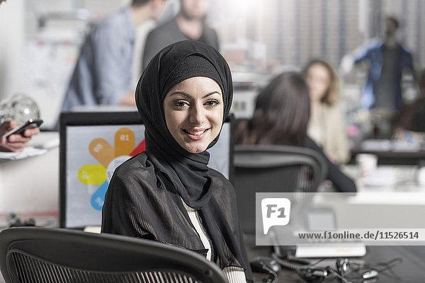 Porträt einer lächelnden jungen Frau mit Hijab im Büro