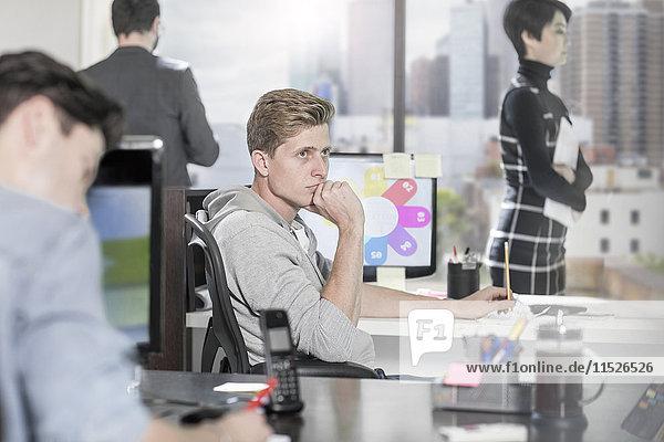 Junger Mann am Schreibtisch  der denkt.