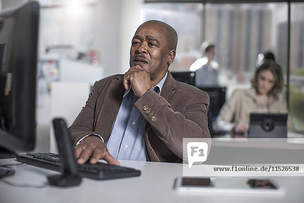Geschäftsmann bei der Arbeit am Computer im Büro