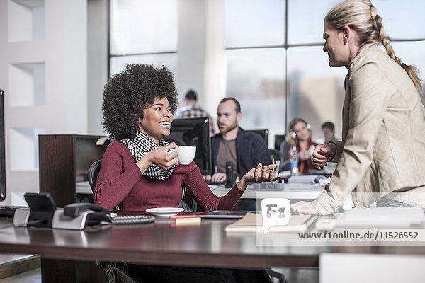 Lächelnde Frau am Schreibtisch im Büro im Gespräch mit Kollegen