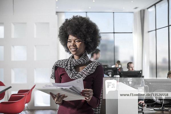 Lächelnde Frau mit Dokumenten im Amt