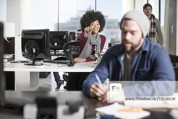Lächelnde Frau am Schreibtisch im Büro zeigt auf Kollegen
